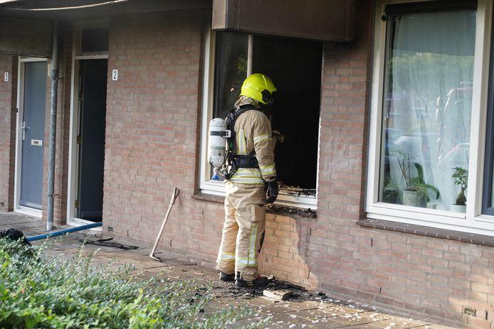 Een brandweerman inspecteert de woning na de brand.