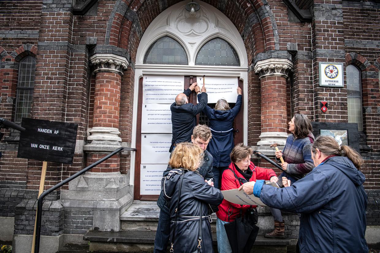 Boze leden van de Lutherse kerk spijkeren hun stelling op de deuren van de kerk in Nijmegen
