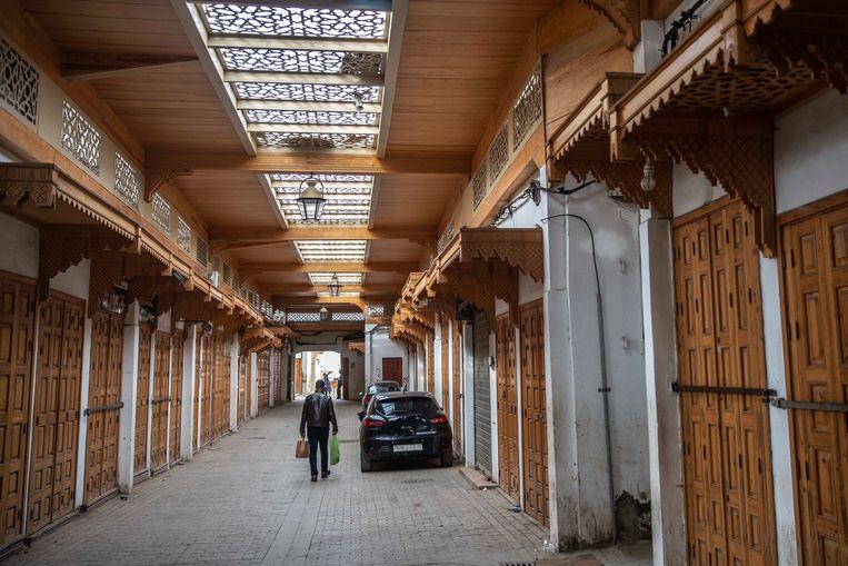 Een man loopt langs gesloten winkels in Rabat. In Marokko zitten er nog 5.000 Belgo-Marokkanen vast.  Beeld AP