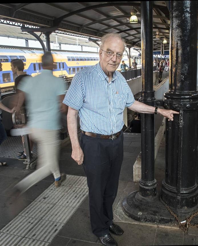 Hans van den Berg bij de gietijzeren paal waar hij tegenaan geduwd is door een passant die rennend zijn trein wilde halen.