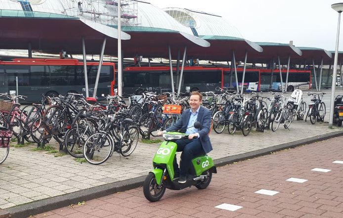 Wethouder Igor Bal mag als eerste op een van de 25 deelscooters rijden