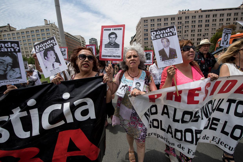 Familieleden van mensen die tussen 1973 en 1990 zijn verdwenen in Chili, tijdens een demonstratie vorig jaar maart.  Beeld AFP