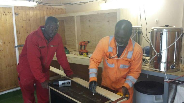Bemanningsleden Francis en Ebanezer bouwen een kast op verzoek van het team van Artsen zonder Grenzen. Beeld Carlijne Vos