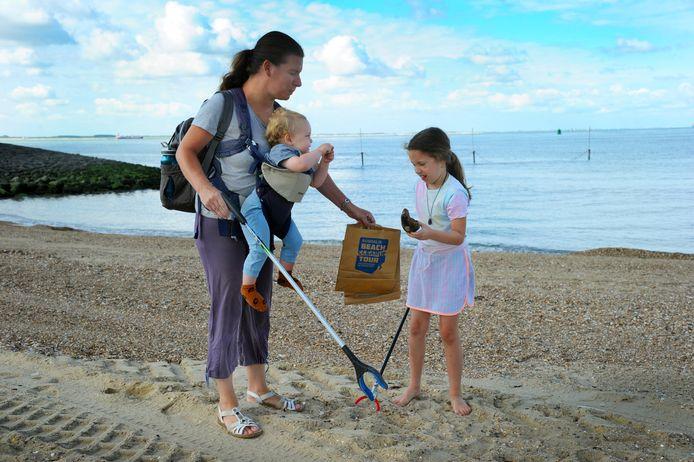 Carla van den Berg en haar dochter  Britt verzamelen afval op het Vlissingse strand terwijl de vijftien maanden oude Joep toekijkt.