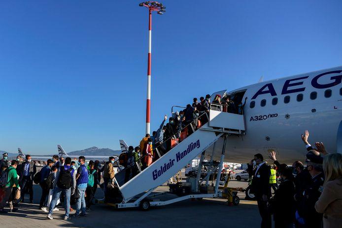 De niet-begeleidde minderjarige vluchtelingen bij het aan boord gaan op de luchthaven van Athene.