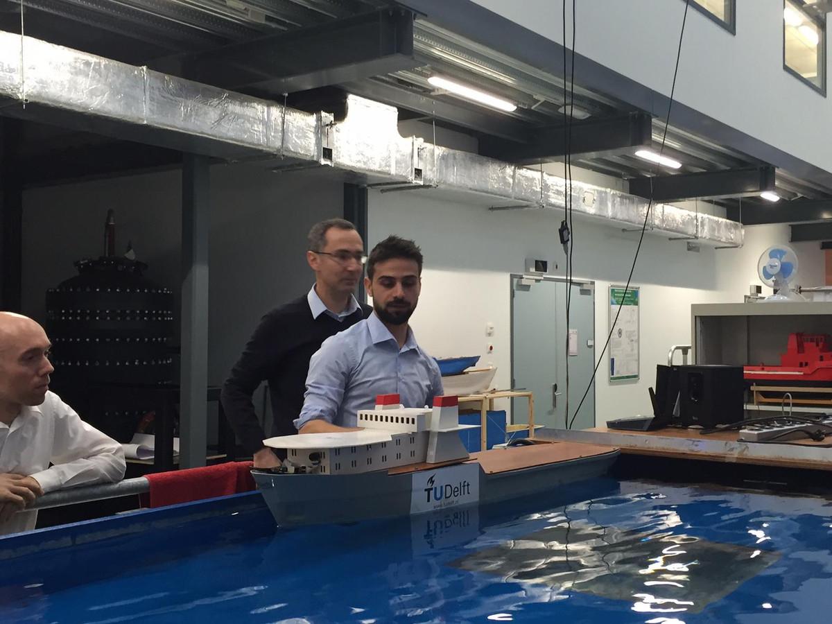Onderzoekers van de TU Delft leggen hun zelfvarende modelschip in het water van één van de bassins van de Faculteit Werktuigbouwkunde. Links Rudy Negenborn, achteraan Milinko Godjevac