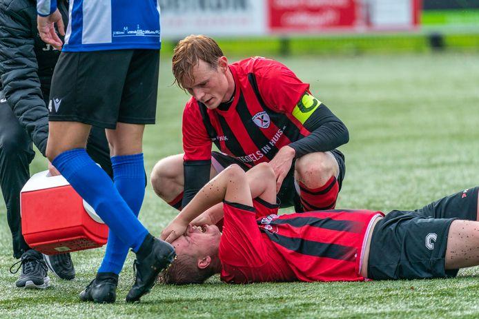 Twan Aarnink ligt op de grond nadat hij een trap tegen zijn hoofd heeft gekregen van een eigen speler. Pieter Mantel staat hem bij. Excelsior Zetten - ESA