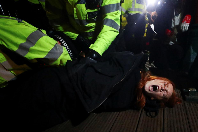 Een vrouw wordt gearresteerd bij de wake op Clapham Common.  Beeld REUTERS