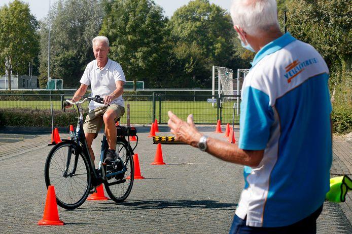 September 2020: een deelnemer rijdt behendig over het hindernisparcours terwijl een vrijwilliger van Veilig Verkeer Nederland instructies geeft.