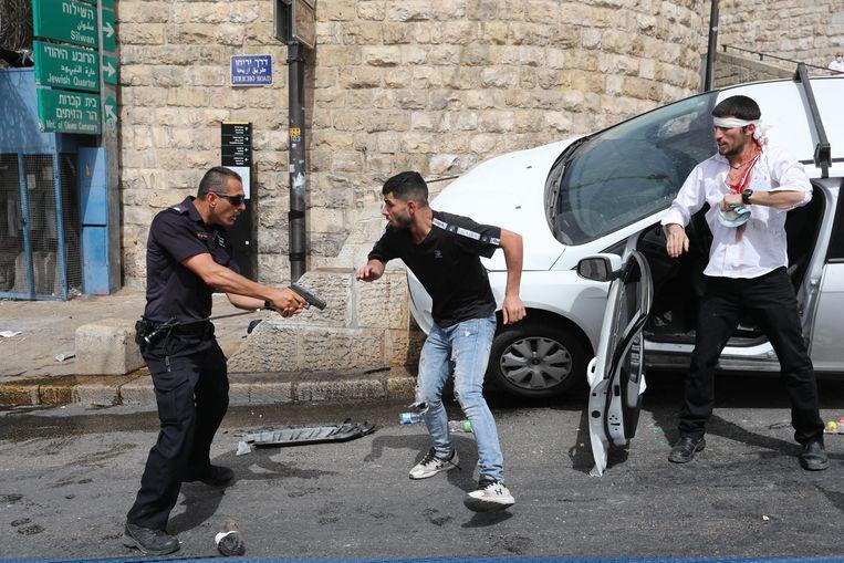 Een Israëlische politieagent (L) richt zijn pistool op een Palestijnse man (M) naast een gewonde Joodse man (R) in Jeruzalem. Beeld EPA
