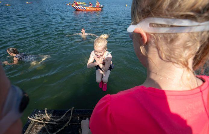 Kinderen leren zwemmen in open water.