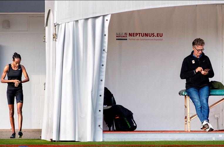 Charles van Commenée, hoofdcoach van de Atletiekunie, checkt zijn telefoon in een tent langs de atletiekbaan van Papendal. Topatlete Sifan Hassan kijkt op haar horloge voordat zij de baan opstapt voor een training. Nog 291 dagen tot Tokio. Beeld Klaas Jan van der Weij