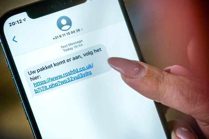 Een telefoon met een frauduleus sms-bericht. Mensen lezen dat ze een pakket ontvangen en moeten op een link klikken waarna hackers de telefoon uit kunnen lezen.