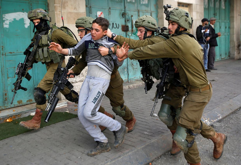 Israëlische soldaten nemen een Palestijns kind mee tijdens gevechten in Hebron, in de bezette Westelijke Jordaanoever. Beeld REUTERS