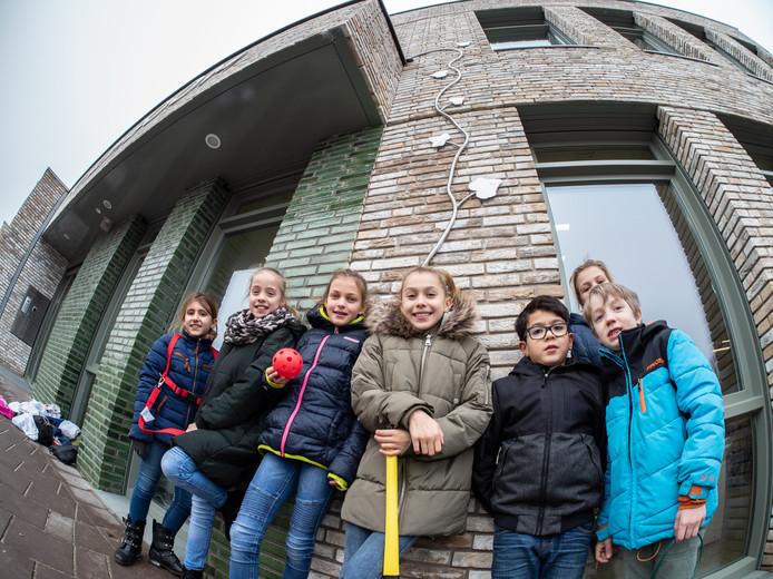 Jalyssa (met gele hockeystick) en schoolgenoten bij het kunstwerk van kunstenaar Reinier Langendijk voor het schoolgebouw van IKC De Klimboom aan de Nesciohove.
