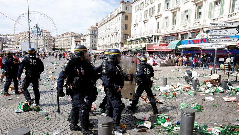 Oproerpolitie houdt de wacht in de oude haven van Marseille voorafgaand aan de EK-wedstrijd Engeland-Rusland, juni 2016. Het plein ligt bezaaid met lege bierflesjes en verpakkingen van Heineken. Beeld EPA