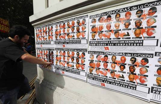 Posters met de tekst 'Dit zijn de daders van de genocide in La Cacha'.
