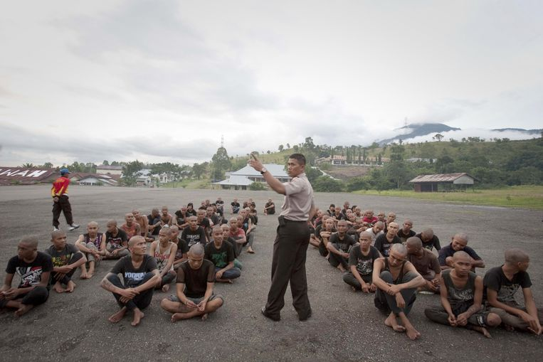 In this photograph taken on December 13, 2011 a police officer lectures a group of detained Indonesian punks at a police school in Aceh Besar in Aceh province. Sharia police are