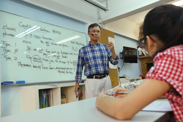 Docent Gilbert Chow Yun-cheung geeft les aan een bijlesinstituut in Hongkong. Beeld South China Morning Post via Getty