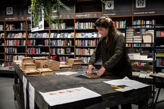 Medewerkster Constance van Dekker van de Vegt Boekverkopers maakt bestellingen klaar. Boekhandels hebben besloten boeken die online zijn besteld zelf naar de klant te gaan brengen.