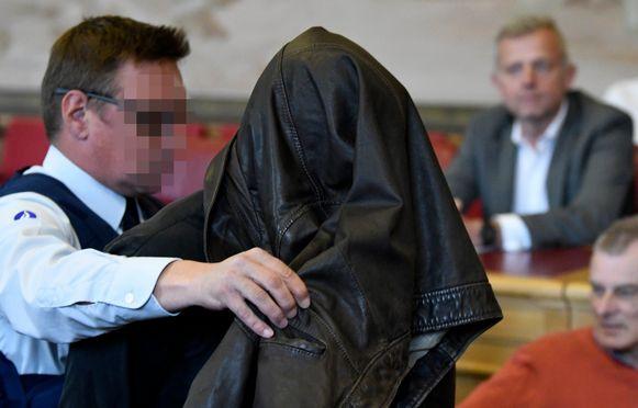 Larmit werd met een jas over zijn hoofd naar binnen geleid.