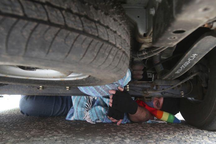 Een betoger gaat onder het busje liggen om de ambtenaren tegen te houden.