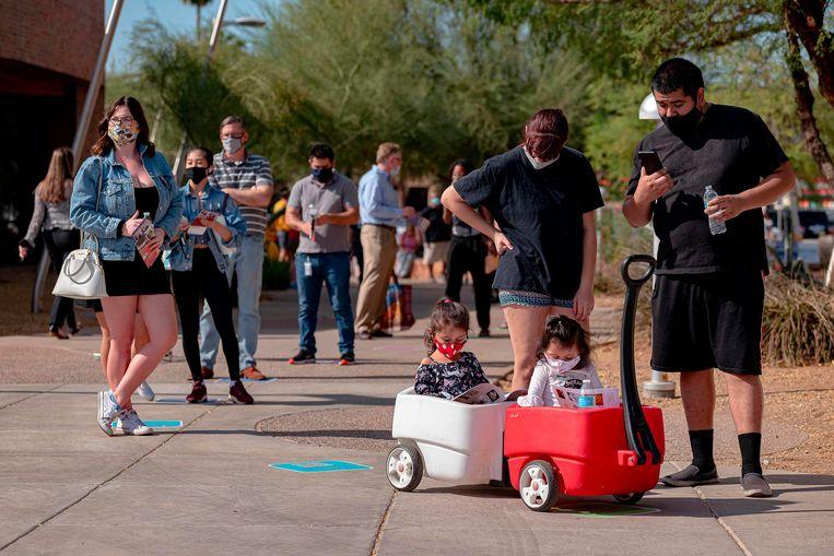 Amerikaanse kiezers staan in de rij voor het stembureau in Tempe, Arizona tijdens de verkiezingen vorig jaar november. Beeld AFP