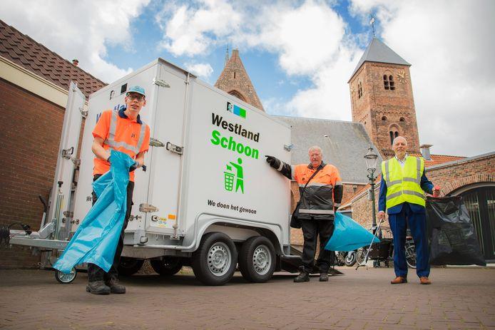 'Afvalwethouder' Leen Snijders (rechts) ruimt samen met medewerkers van Patijnenburg zwerfvuil op in Naaldwijk.