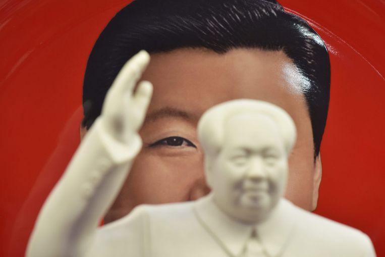 In een souvenirwinkel in Peking hangt het portret van Xi achter een beeldje van Mao. Beeld AFP