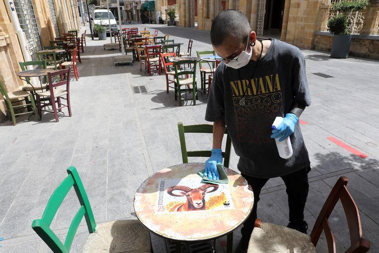 Een medewerker desinfecteert een terras in de Cypriotische hoofdstad Nicosia. (21/05/2020)