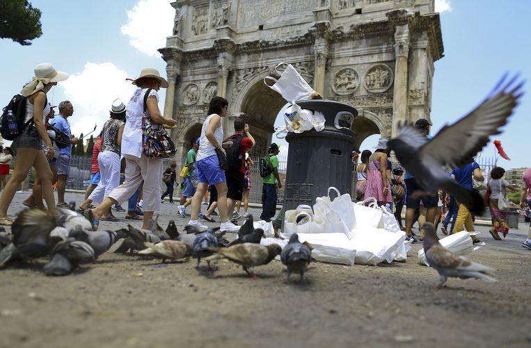 Toeristen lopen langs een uitpuilende vuilnisbak aan de Boog van Constantijn. Beeld REUTERS