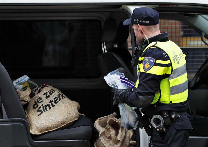 Leden van Pegida verkleed als zwarte piet wordt aangehouden in Apeldoorn tijdens de intocht van Sinterklaas.