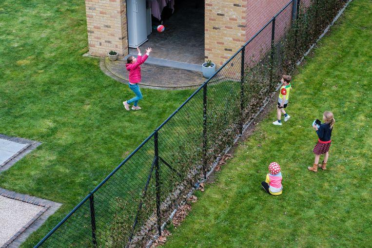 Creativiteit troef. In Zomergem spelen kinderen samen een balspel over de omheining tijdens lockdown light. Beeld Wouter Van Vooren
