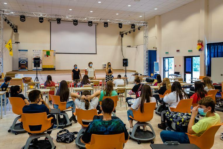 De decaan van de hogeschool Mons. Antonio Bello in Molfetta verwelkomt studenten voor hun eerste les, op 14 september. Mondkapjes worden in Italië nog met religieuze ijver gedragen. Beeld Getty Images