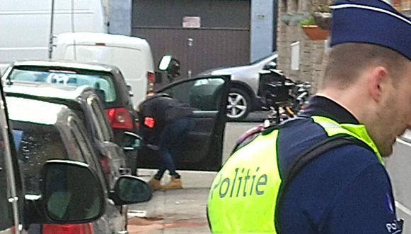 Een speurder van de moordbrigade doorzoekt een geparkeerde auto in de Dijlestraat.