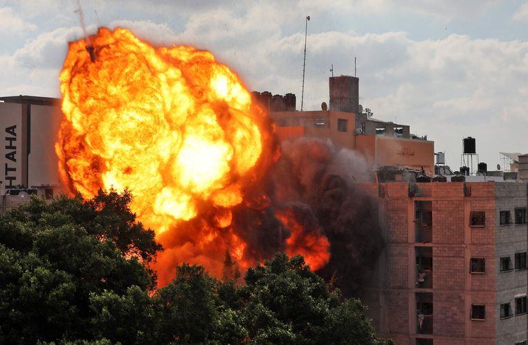 Een gebouw in Gaza stad wordt verwoest door een luchtaanval van de Israëliërs. Beeld AFP