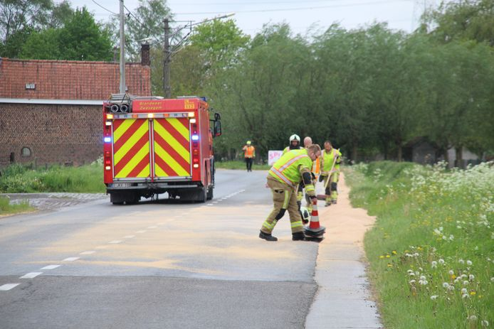 De brandweer ruimt een lading haver van de rijbaan