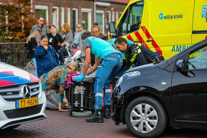 Omstanders kijken toe terwijl hulpdiensten zich ontfermen over de omgevallen scootmobiel en de bestuurder. De mensen op de foto waren niet betrokken bij het ongeluk.