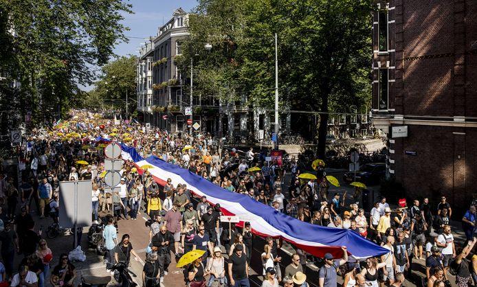 Demonstranten op de Dam tijdens de manifestatie Samen voor Nederland. De actie richt zich tegen vrijheidsbeperkende coronamaatregelen en medische apartheid.