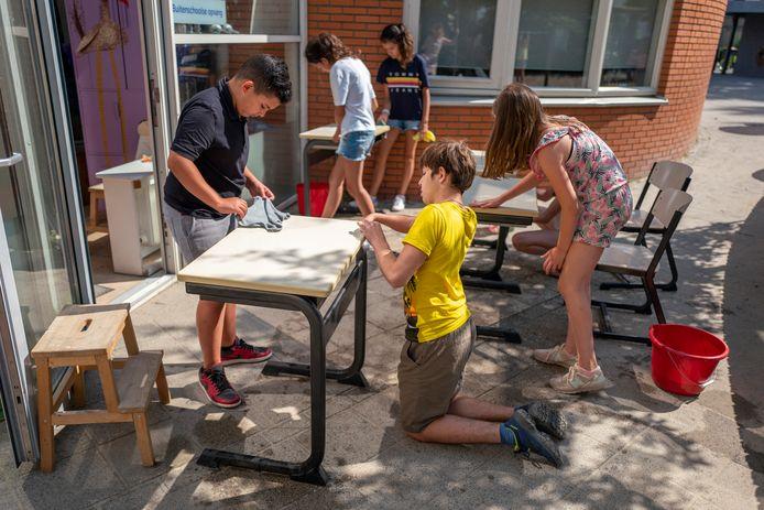 Op de laatste schooldag voor kinderen van De Petteflet wordt er hard gepoetst om alle tafels en stoelen goed schoon te maken.