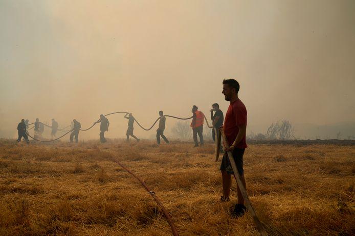 Vrijwilligers houden de brandslang vast ten noorden van Athene.