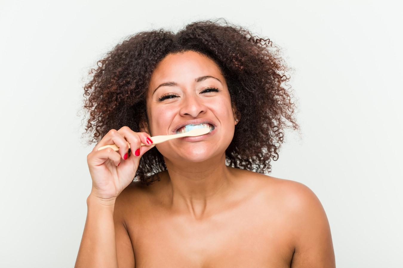Jonge vrouw poetst haar tanden.