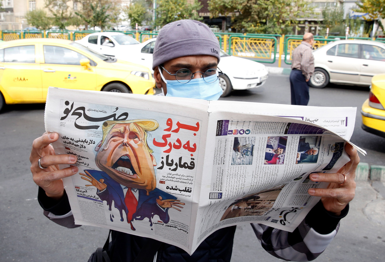 Een man leest een Iraanse krant met daarin een cartoon van president Trump. De kop erboven: 'loop naar de hel, gokker'. Wat zouden wij doen als in Islamitische kranten God zou worden bespot, vraagt een lezer zich af.  EPA/ABEDIN TAHERKENAREH