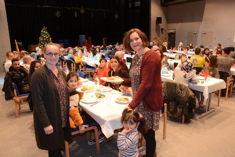 Ingrid Pierré van geefwinkel Feniks en schepen Veerle Beernaert staken zaterdag mee de handen uit de mouwen voor een kerstdiner voor een honderdtal mensen in armoede.