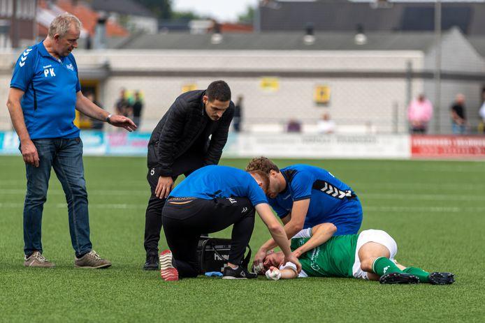 Jasper Scholten wordt op het veld behandeld aan zijn hoofd.