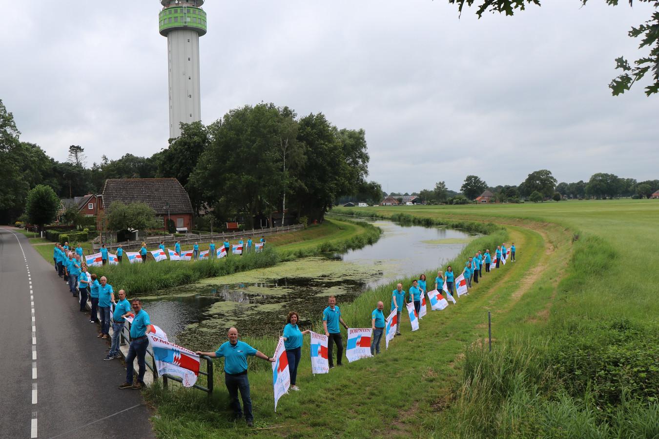 Bestuurs- en commissieleden van het Dorpsfeest Markelo vormen bij de Schipbeek een 'lint' met vlaggen, vrij naar de regel uit het Markelo's Volkslied.