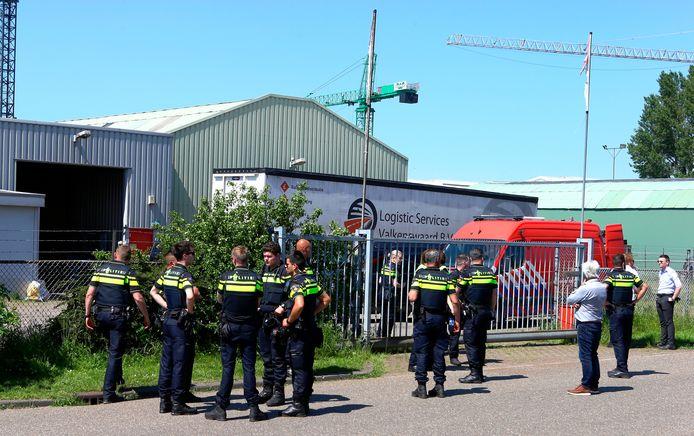 Volop politie voor het hek van het terrein waar de loods met het drugslaboratorium staat. Ook de brandweer is aanwezig.