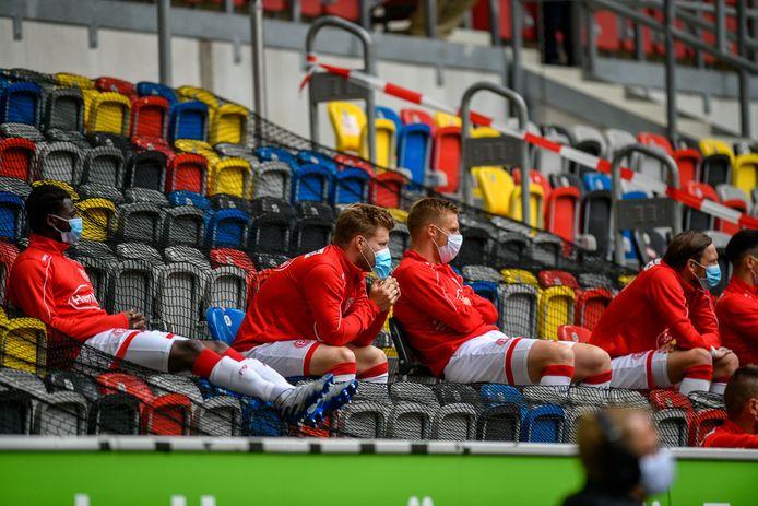 De wisselspelers van Fortuna Düsseldorf volgen met mondkapjes op de verrichtingen van hun ploeggenoten.