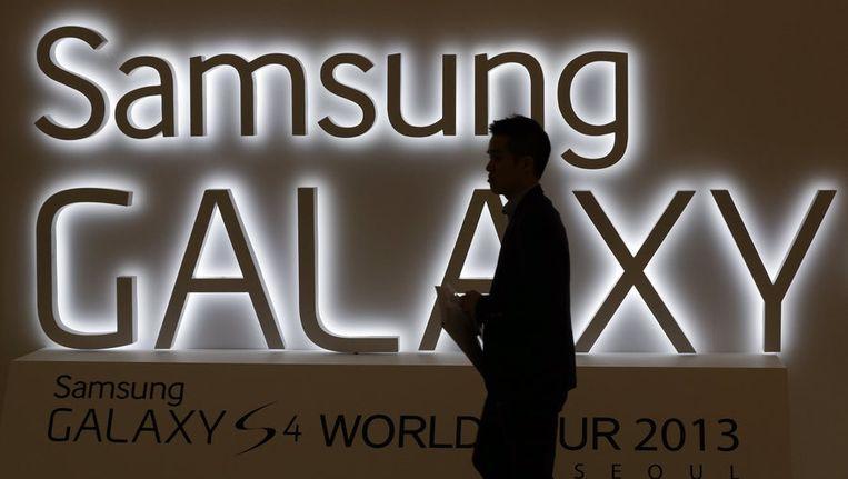 Een man loopt voorbij het logo van Samsung Galaxy Beeld ap