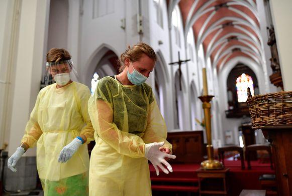 De verpleegsters van Geneeskunde voor het Volk maken zich klaar voor coronatesten in het bijzondere decor van de Sint-Rochuskerk.